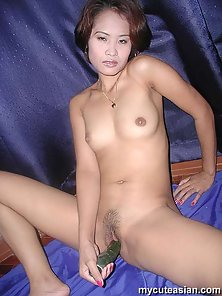 Amateur inserts cucumber in her asian pussy
