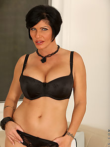Sexy black haired cougar with big tits pleasures her pussy in stockings