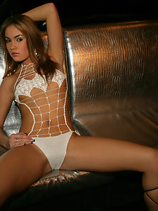 Cute young brunette posing naked on leather couch