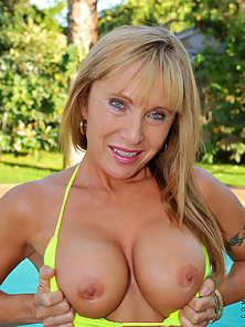 Hot mom with massive tits enjoys her pool while floating around naked with a finger in her mature pu